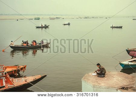 Varanasi, India: Romantic Evening On Riverside With Riverboats In Fog Of Ganges River And Local Peop