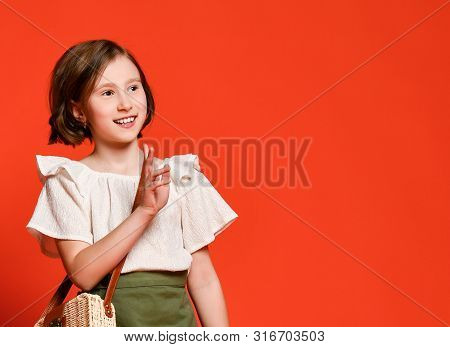 Little cute girl in khaki skirts and light blouse with a straw hat and a straw bag posing on a red terracotta background. poster