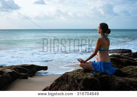 Young woman meditating, practicing yoga and pranayama with gyan mudra at the beach. Lotus yoga pose with gyan mudra. Caucasian woman sitting on the rock. Sunset time. Yoga retreat in Bali, Indonesia
