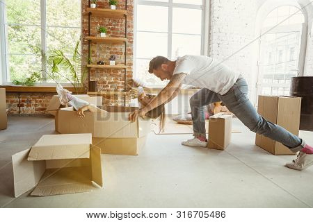 Young Couple Moved To A New House Or Apartment. Having Fun With Cardboard Boxes, Relaxing After Clea