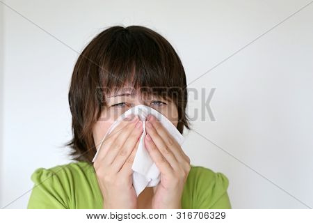 Sick Woman With Sore Eyes Sneezing And Blowing Her Nose In A Napkin. Concept Of Colds And Flu, Runny