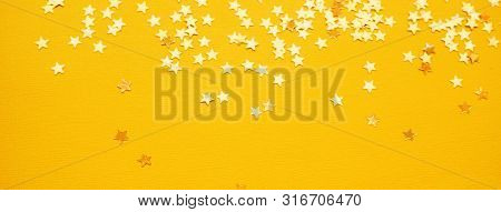 Golden Stars Glitter On Yellow Background. Festive Holiday Bright Backdrop. Design For Your Ad, Post