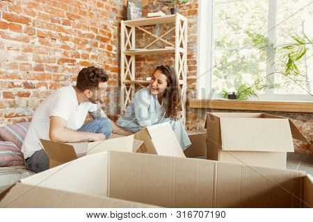 Young Couple Moved To A New House Or Apartment. Unpacking Cardboard Boxes Together, Having Fun At Mo