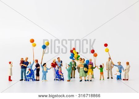Miniature People Holding Balloon Isolated On White Background