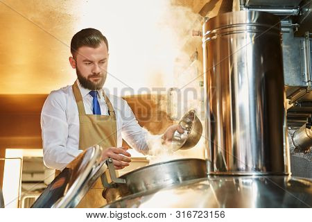 Serious Man Brewing Beer. Professional Brewer In White Shirt And Apron Working In Beer Manufacturing
