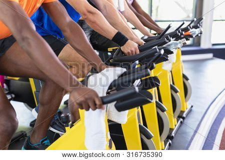 Mid section of diverse fit people exercising on exercise bike in fitness center. Bright modern gym with fit healthy people working out and training at spin class