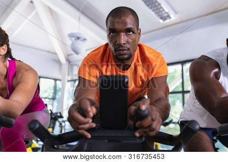 Close-up of African-american fit men exercising on exercise bike in fitness center. Bright modern gym with fit healthy people working out and training at spin class