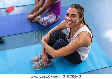 High angle of Caucasian fit woman relaxing on a exercise mat in fitness center. Bright modern gym with fit healthy people working out and training