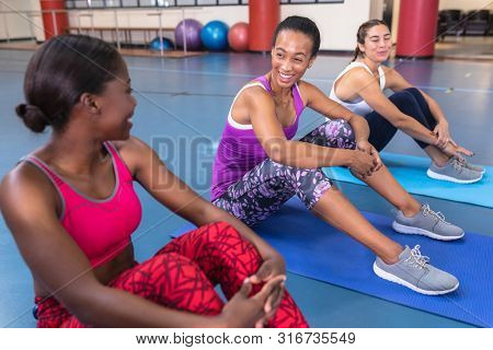 Side view of diverse fit women interacting with each other in fitness center. Bright modern gym with fit healthy people working out and training