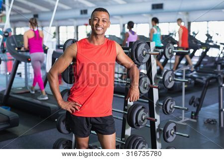 Portrait of happy African-american man looking at camera while standing in fitness center. Bright modern gym with fit healthy people working out and training