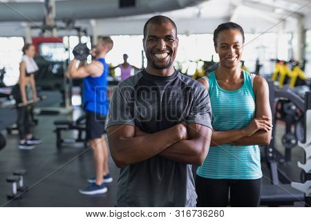 Portrait of African-american fit man and woman standing with arms crossed in fitness center. Bright modern gym with fit healthy people working out and training