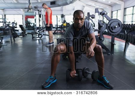Front view of African-american fit man exercising with dumbbells in fitness center. Bright modern gym with fit healthy people working out and training