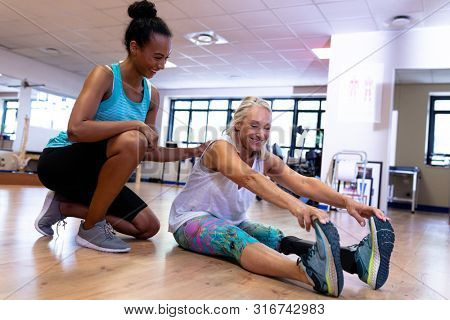Side view of Happy African-american female trainer assisting disabled active Caucasian senior woman to exercise in sports center. Sports Rehab Centre with physiotherapists and patients working