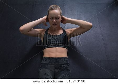 High angle view of Caucasian woman doing crunches in fitness center. Bright modern gym with fit healthy people working out and training