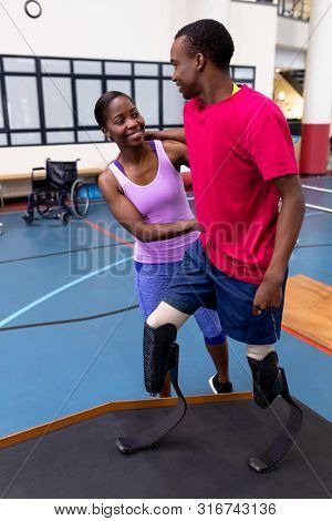 Front view of Happy African-american physiotherapist helping disabled African-american man walk with prosthetic leg on ramp in sports center. Sports Rehab Centre with physiotherapists and patients