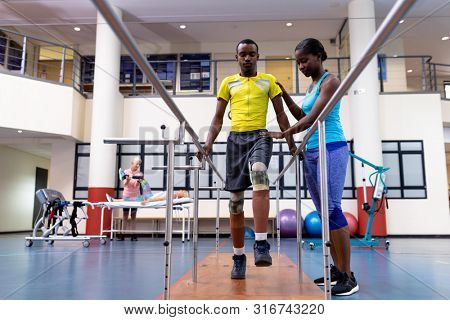 Low angle view of African-american physiotherapist helping disabled African-american man walk with parallel bars in sports center. Sports Rehab Centre with physiotherapists and patients working