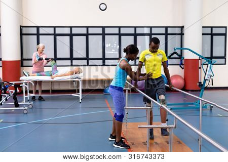 High angle view of African-american Female physiotherapist helping disabled African-american man walk with parallel bars in sports center. Sports Rehab Centre with physiotherapists and patients
