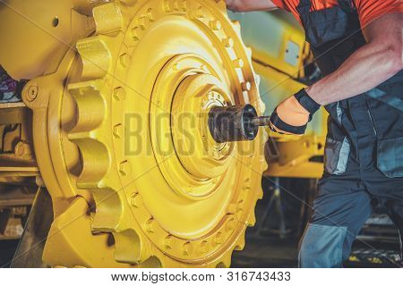 Bulldozer Pro Mechanic. Caucasian Construction Machines Technician Rebuilding Bulldozer.