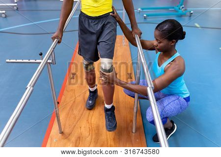 High angle view of African-american physiotherapist assisting disabled African-american man walk with parallel bars in sports center. Sports Rehab Centre with physiotherapists and patients working