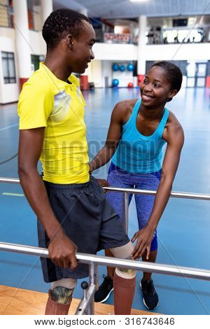 Front view of Happy African-american female physiotherapist helping disabled African-american man walk with parallel bars in sports center. Sports Rehab Centre with physiotherapists and patients