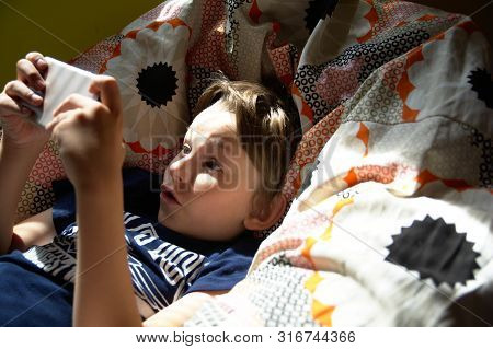 A Portrait Of Surprised Boy With Mobile Phone In The Armchair. The Kid Use Phone And Play Game, Chil