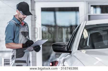 Caucasian Car Service Worker Making Documentation About Vehicle Issues. Car Maintenance In The Autho