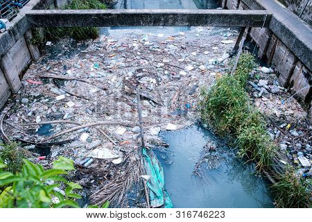 Ecology Watercourse River Canal With Garbage And Plastic