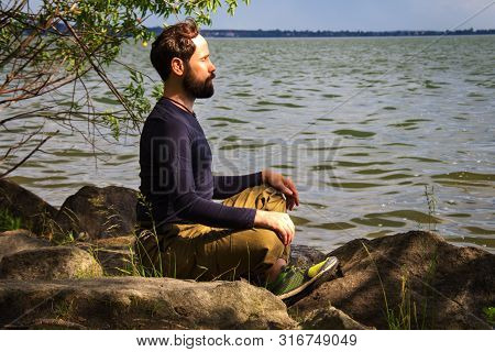 A Bearded Man Is Meditating By The River Emotional Meditating Lifestyle. Introspection Relaxing