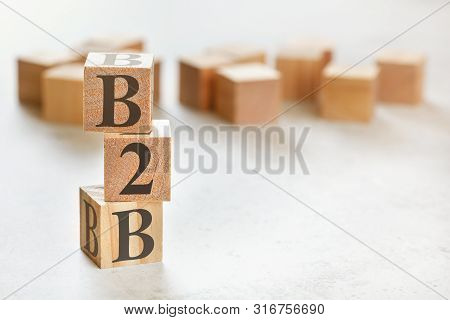 Three Wooden Cubes With Letters B2b Means Business To Busines , On White Table, More In Background,
