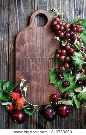 Beautiful Solid Walnut Cutting Board With Fresh, Red, Organic Homegrown Fruit. Plums, Grapes And Str