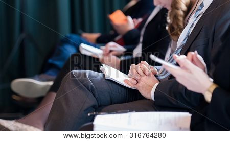 closeup shot of business people hands using pen while taking notes on education training during business seminar at modern conference room