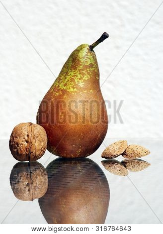 Still Life With Ripe Pear, Walnut And Salted Almonds In Their Nutshells Against High Key Background