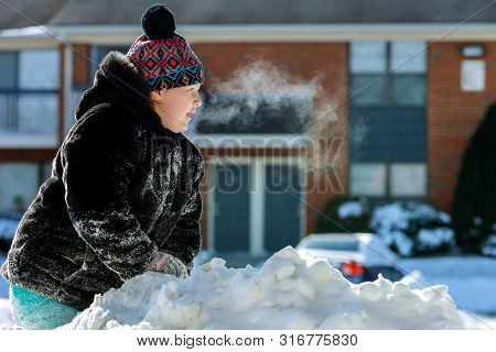 Girl Playing With Snow Outside. Steam Comes From The Mouth.