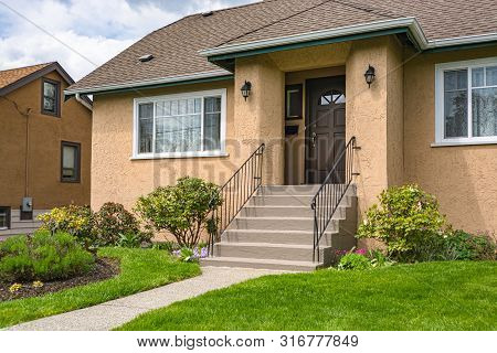 Entrance Of Average Family House With Green Lawn In Front