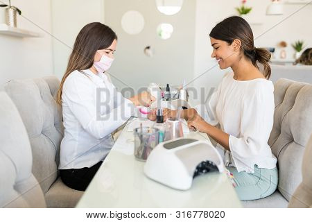Female cosmetician working on smiling client's nails at salon poster