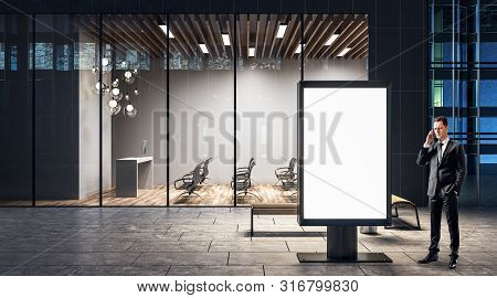 Businessman Talking On The Cell Phone Near Outdoor Blank White Advertising Banner.