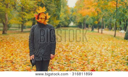 Strange Hipster Man In Black Parka Jacket With Fall Leaves On Face Standing In Autumn Park. Funny Tr