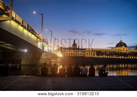Lyon, France - July 18, 2019: Young French People Sitting On Riverbank Of Quais De Rhone, Facing Hot