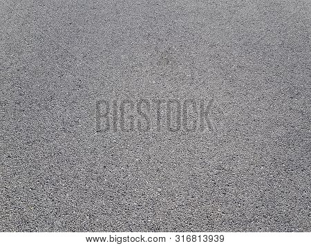 Light Gray Asphalt For Pavement. The Surface Of The Asphalt Is Smooth. Tarmac Construction Material.