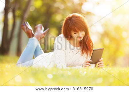 Young woman with pad in the autumn park. Beauty nature scene with colorful background at fall. Outdoor lifestyle at fall season. Happy smiling woman relax on green grass
