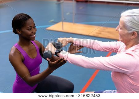 Side view of Happy African-american female trainer assisting disabled Caucasian senior woman to exercise with dumbbell in sports center. Sports Rehab Centre with physiotherapists and patients working