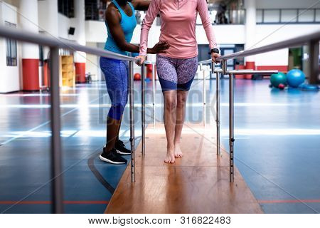 Low section of African-american female physiotherapist helping disabled Caucasian senior woman walk with parallel bars in sports center. Sports Rehab Centre with physiotherapists and patients working