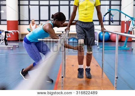 Side view of African-american Female physiotherapist assisting disabled African-american man walk with parallel bars in sports center. Sports Rehab Centre with physiotherapists and patients working