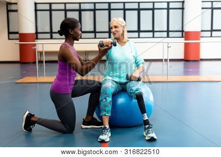 Side view of African-american Female trainer assisting disabled Caucasian senior woman to exercise with dumbbell in sports center. Sports Rehab Centre with physiotherapists and patients working
