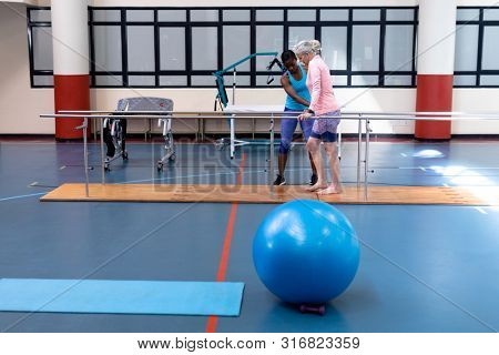 Side view of African-american female physiotherapist helping disabled Caucasian senior woman walk with parallel bars in sports center. Sports Rehab Centre with physiotherapists and patients working