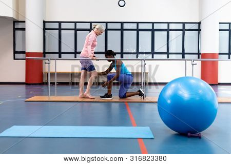Side view of African-american female physiotherapist assisting disabled Caucasian senior woman walk with parallel bars in sports center. Sports Rehab Centre with physiotherapists and patients working