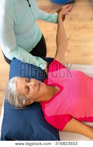 High angle view of female physiotherapist giving arm massage to active senior woman in sports center. Sports Rehab Centre with physiotherapists and patients working together towards healing