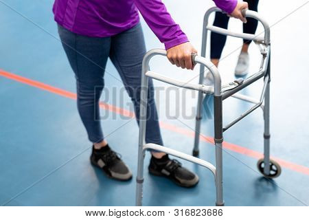 Low section of Disabled senior woman walking with walker in sports center. Sports Rehab Centre with physiotherapists and patients working together towards healing
