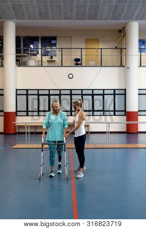 Front view of female physiotherapist helping disabled senior woman walk with walker in sports center. Sports Rehab Centre with physiotherapists and patients working together towards healing