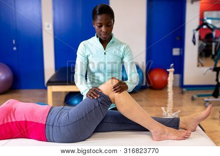Front view of female physiotherapist giving leg massage to active senior woman in sports center. Sports Rehab Centre with physiotherapists and patients working together towards healing